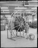 Aero-Motive Manufacturing Company, interior, woman standing next to large powered hose reel in warehouse