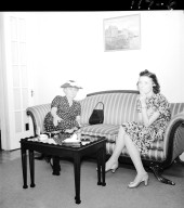 Two women seated on formal couch, one smoking