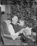 Gerrit Vander Meer reading to toddler in front of Christmas tree