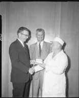 Peter Eckrich & Sons, Inc., two executives presenting watch to employee in butcher coat