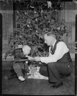 Gerrit Vander Meer and toddler on tricycle in front of Christmas tree