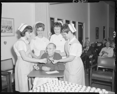 Two nurses and two aids help an elderly man with cookies and punch at a Valentine's Day Party at unknown nursing home
