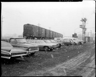 Cars parked in lot near train tracks, Georgia Pacific Railway cars on tracks, Parchment