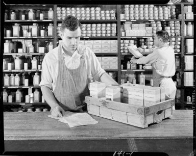 Two men pulling Upjohn pharmaceuticals from stocking shelves