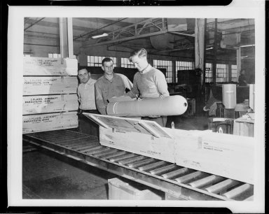 Kalamazoo Stove Company, workers loading parachute flare into wooden crate