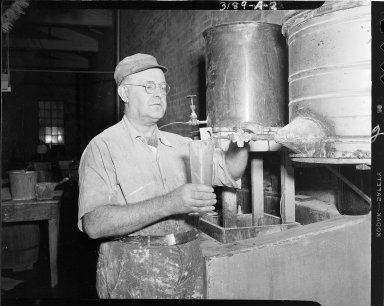 St. Regis Paper Company, employee measuring liquid in company plant