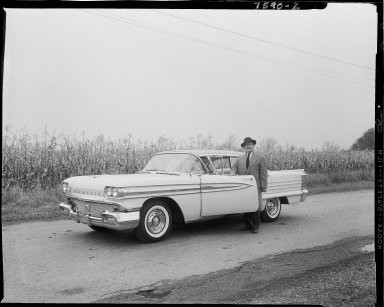 Mr. Black standing next to his new Oldsmobile Super 88