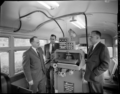 Hammond Machinery Builders, Inc., Electrolytic Carbide Tool Grinder on display and salesmen in bus