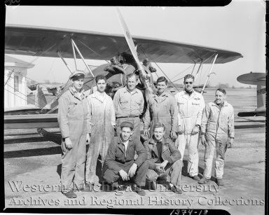 Western Michigan Flying Service, group portrait of mechanics standing in front of an airplane
