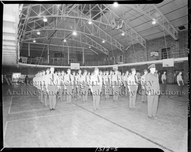 Cadets standing at attention inside gymnasium