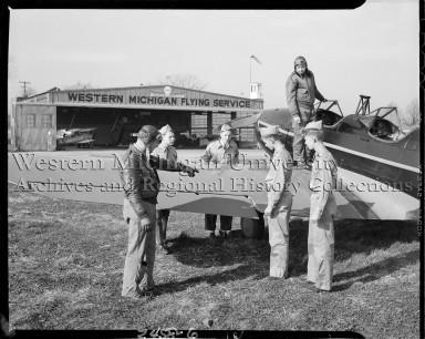 Air scouts and pilots examining airplane