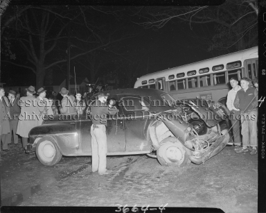 Crowd around a car and bus accident on East Main Street