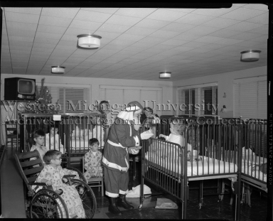Santa Claus handing out gifts to children in the hospital
