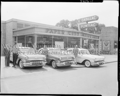 Paper City Motor Sales, exterior with winners of Pontiac Contest posing next to cars
