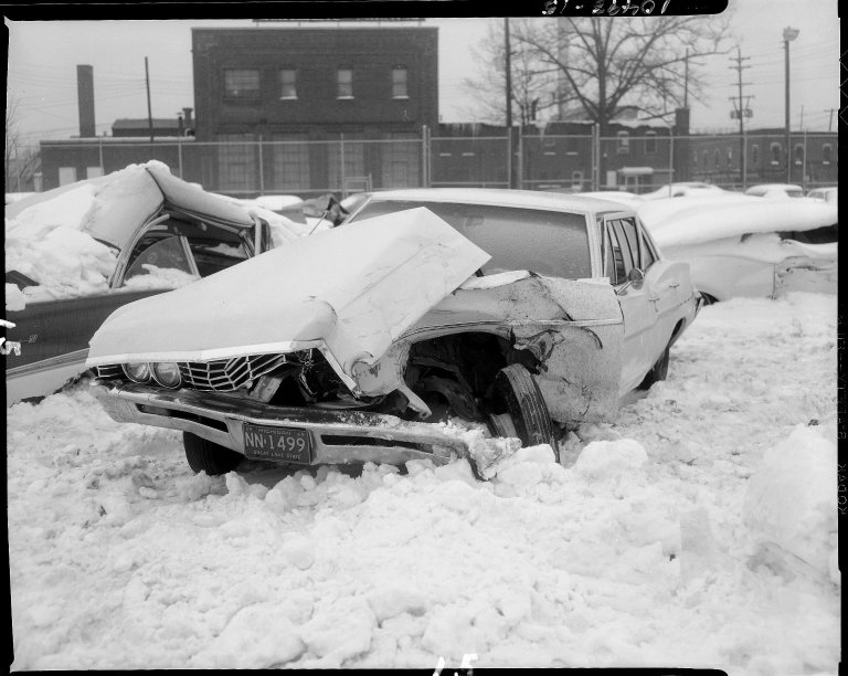 Wrecked automobile parked in snow in Kalamazoo city lot