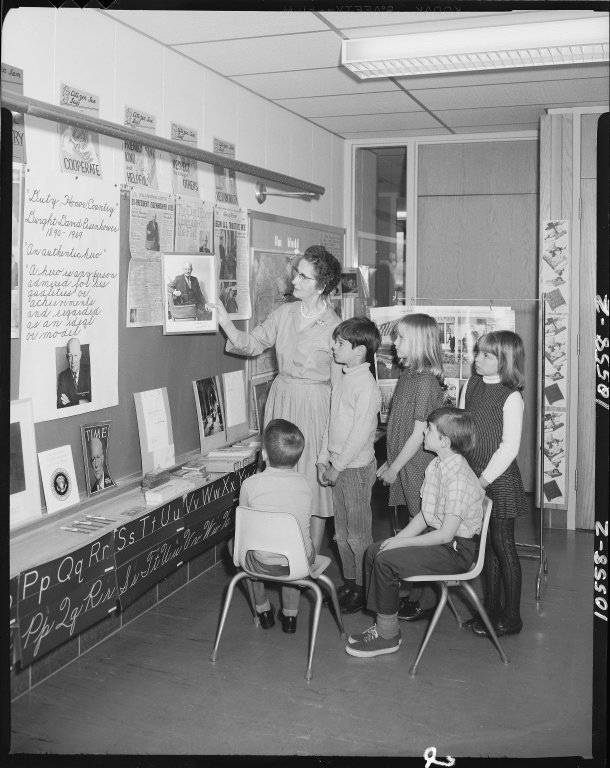 Winchell School, Mrs. Mildred Borton with students looking at picture of President Eisenhower
