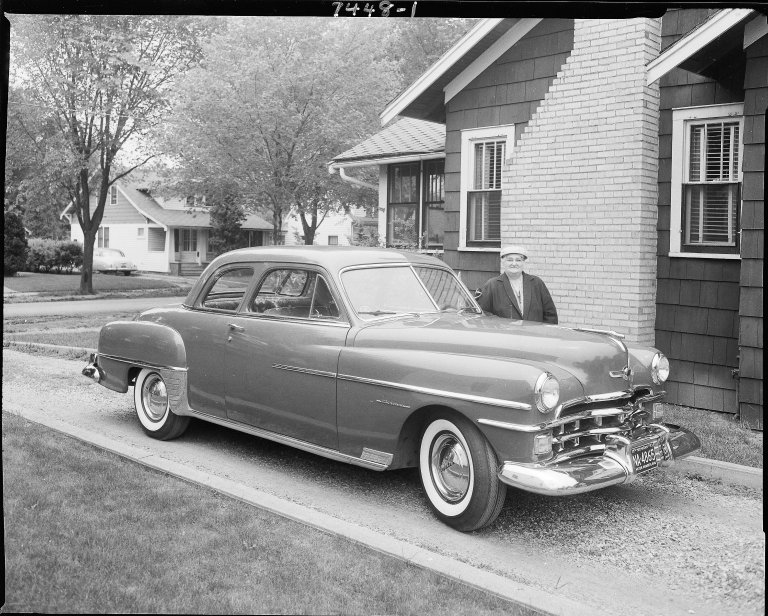 Chrysler car with woman at side of house