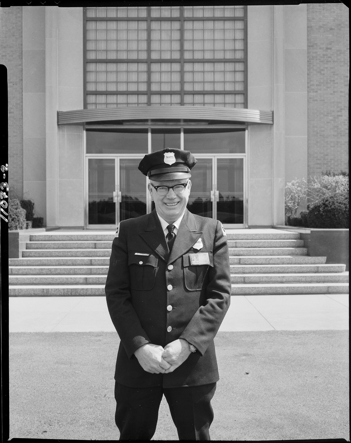 Raymond Gernaat, Upjohn Company security guard in front of an Upjohn building