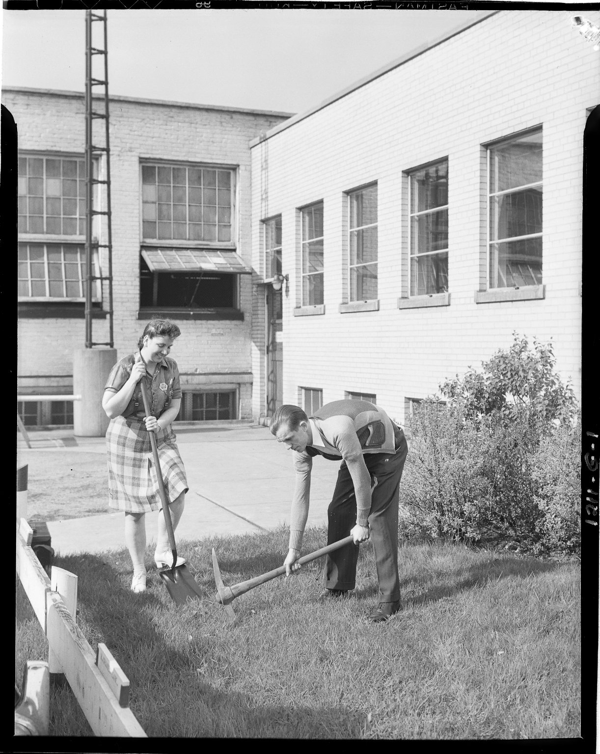 Two people digging in lawn to create a hole for flag pole