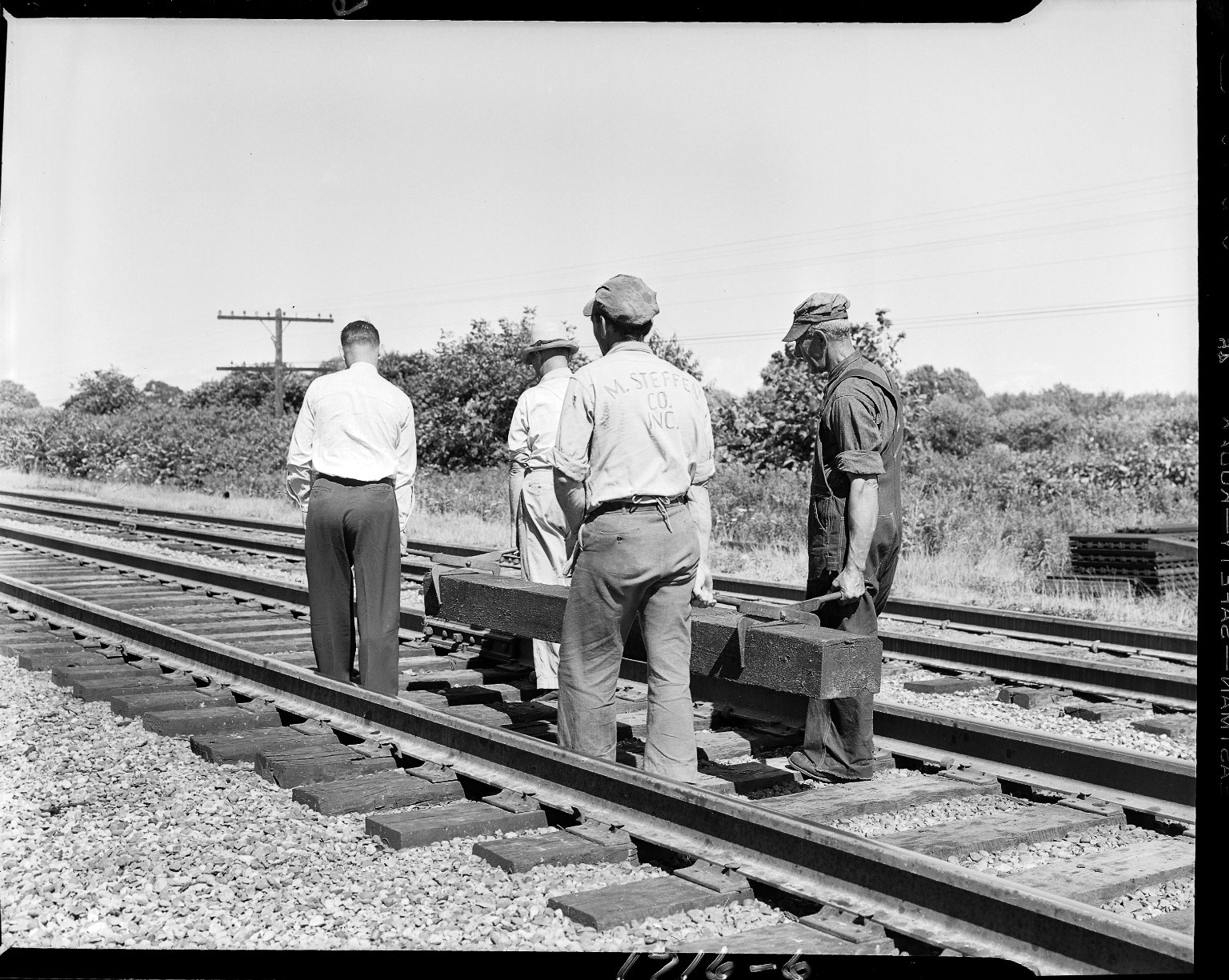 Men moving railroad tie on railroad tracks
