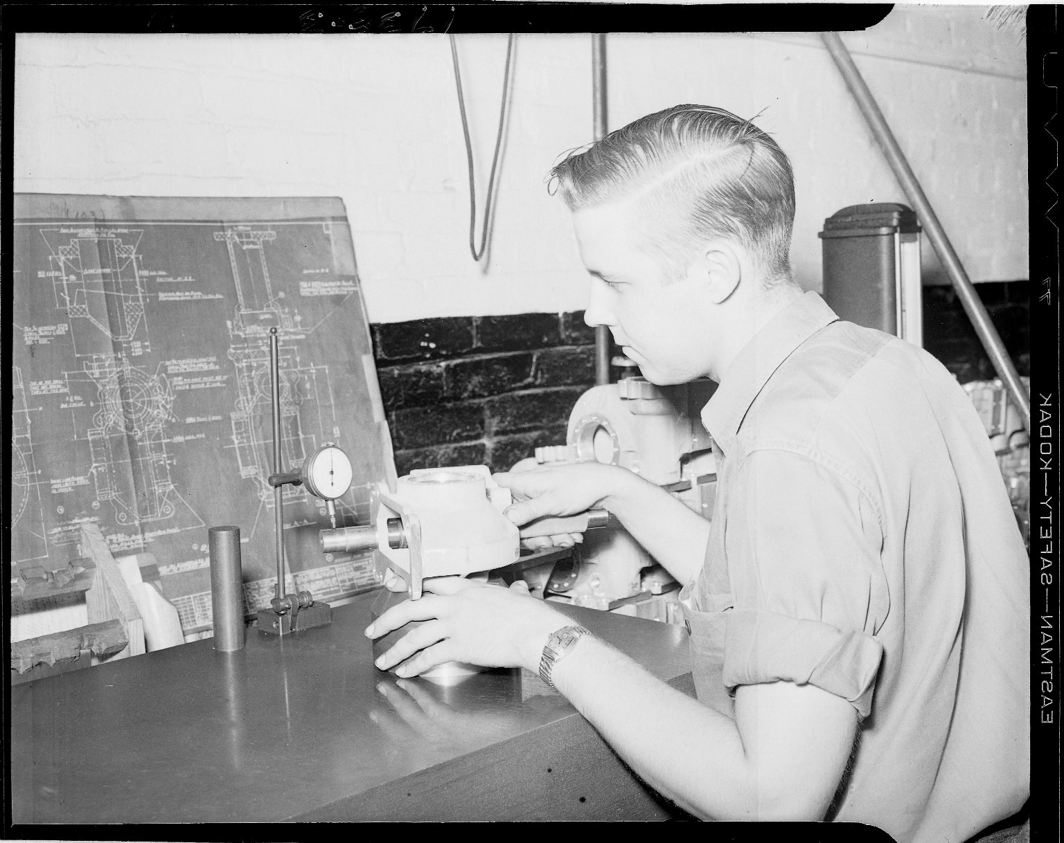 Technician checking industrial part to specification drawing
