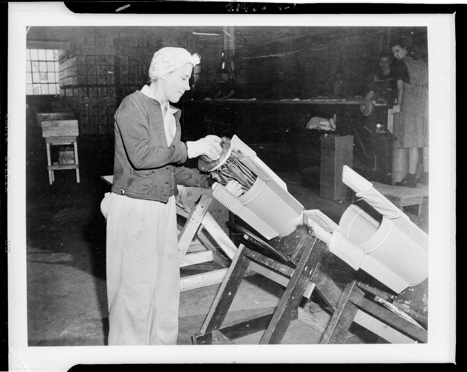 Kalamazoo Stove Company, worker packing parachute into cylinder