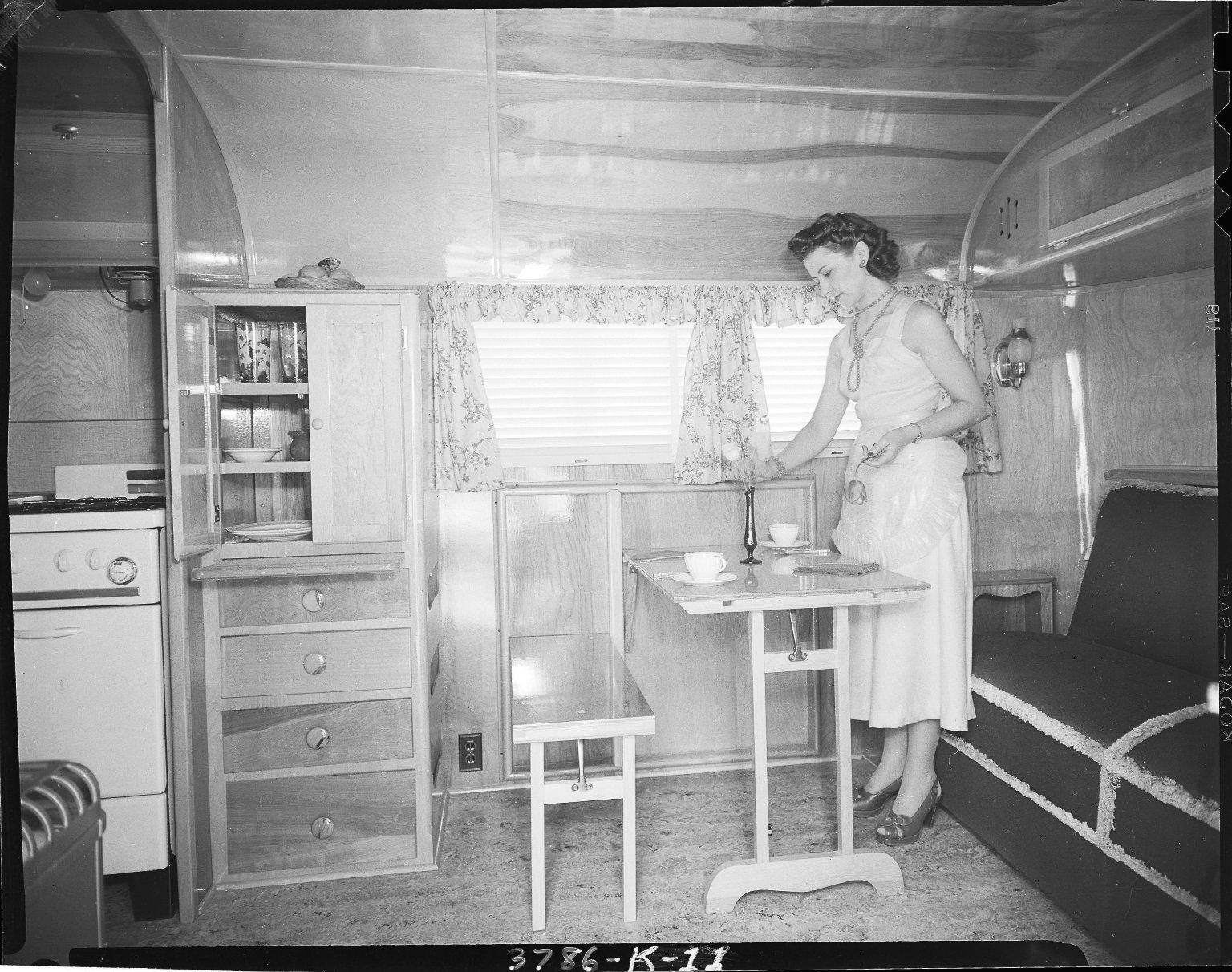 Kozy Coach Company, trailer interior, woman setting table