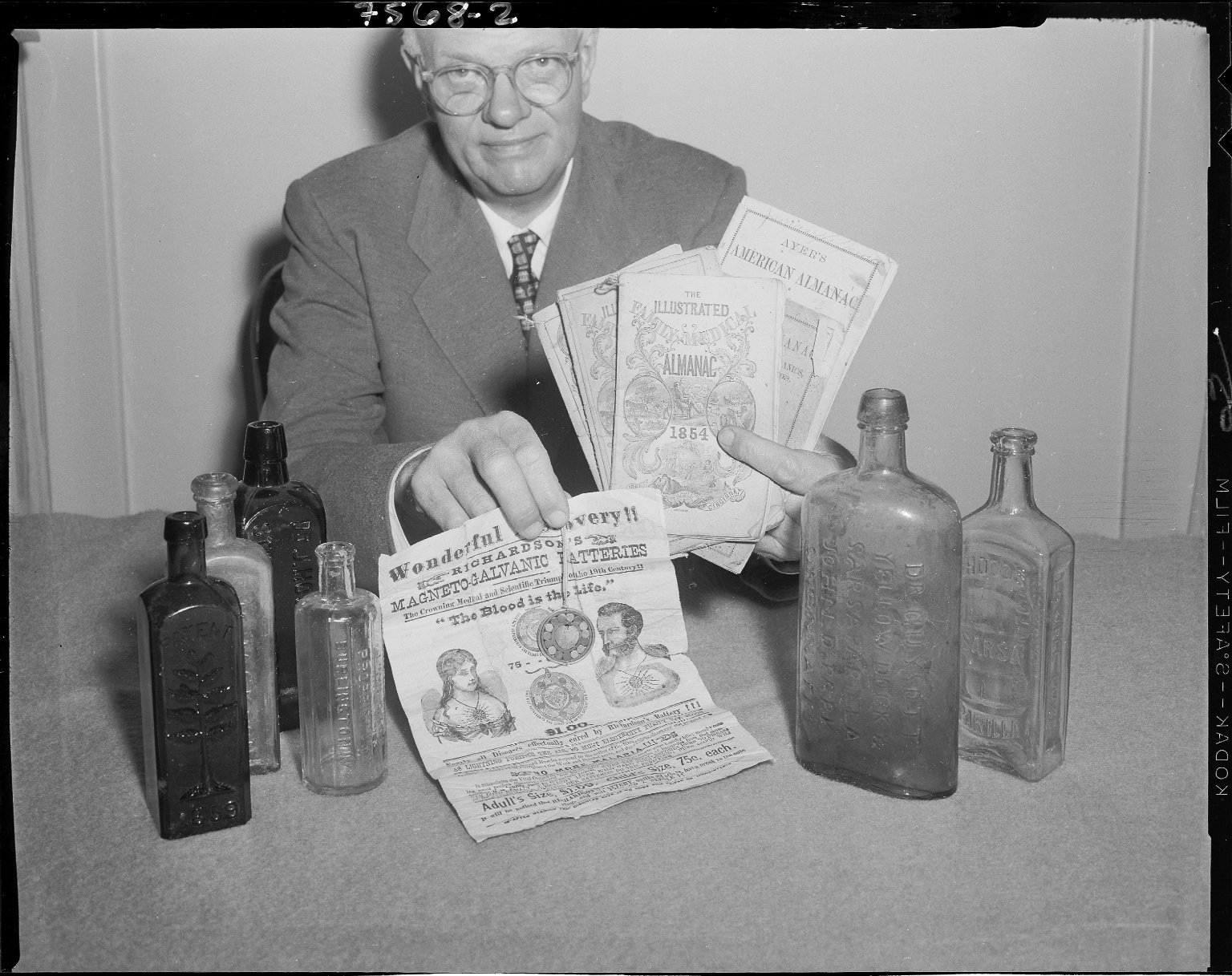 Man displaying antique patent medicine bottles, broadside
