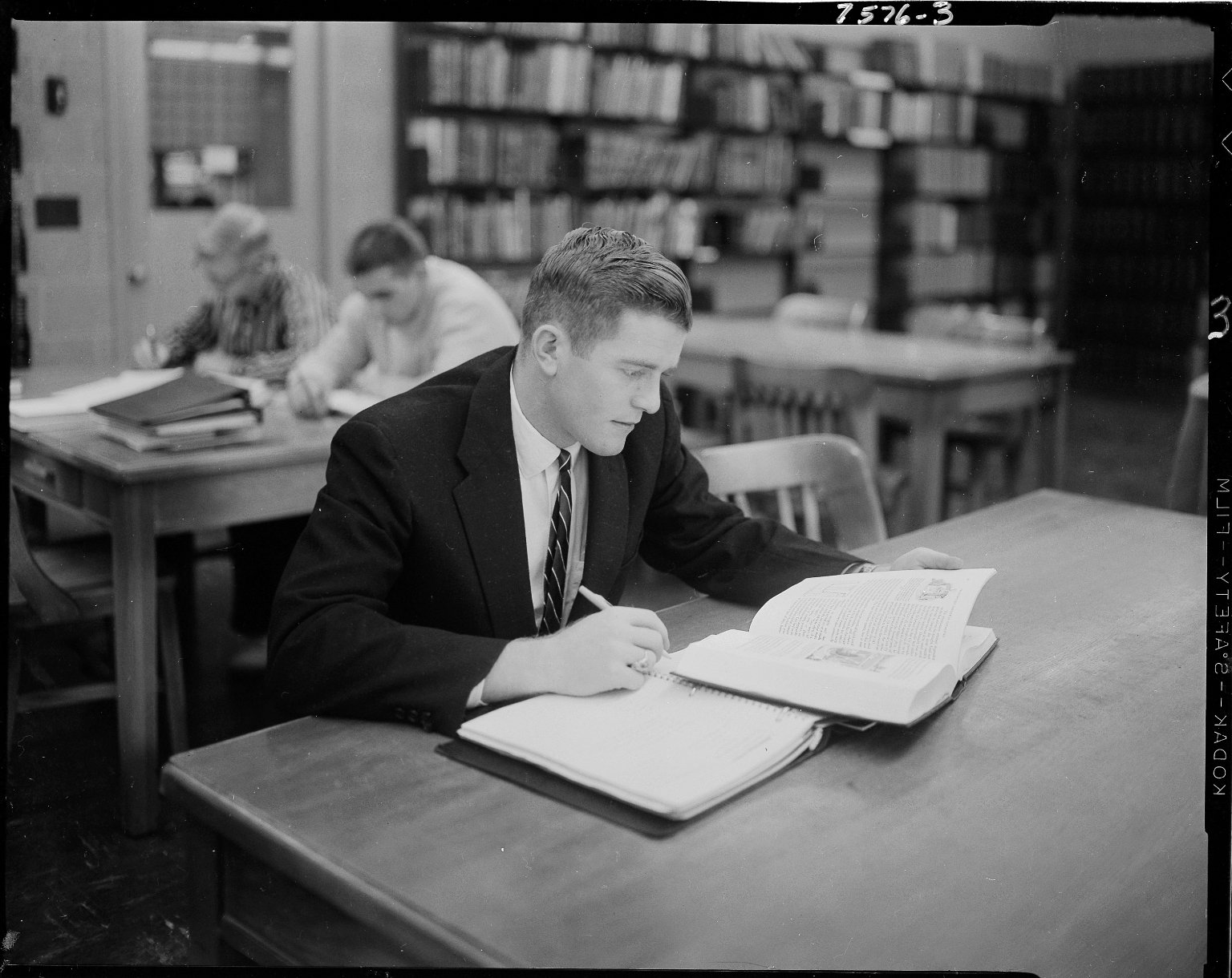 Male student working at a library table