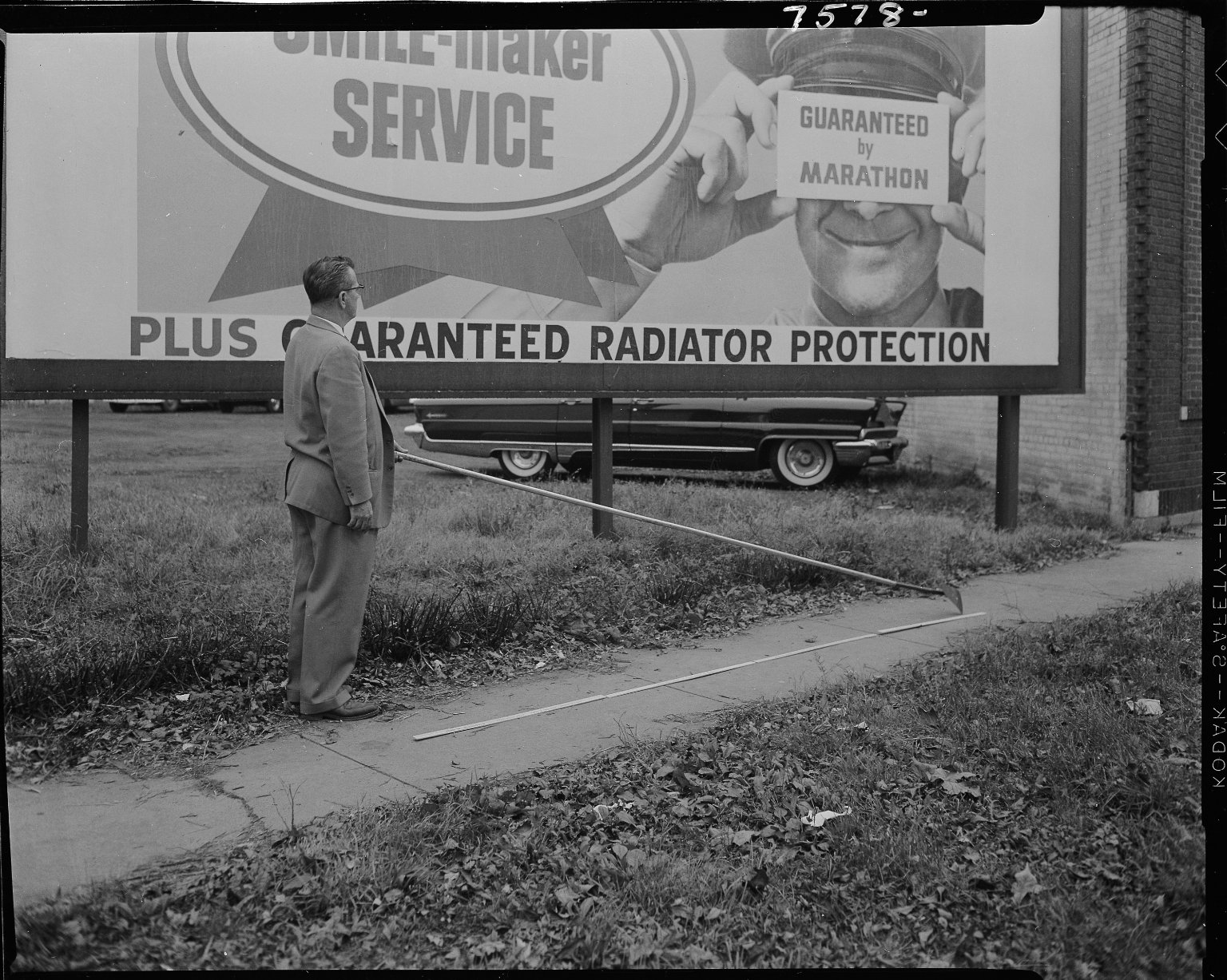 Man holding billboard scraping tool in front of Marathon Oil billboard