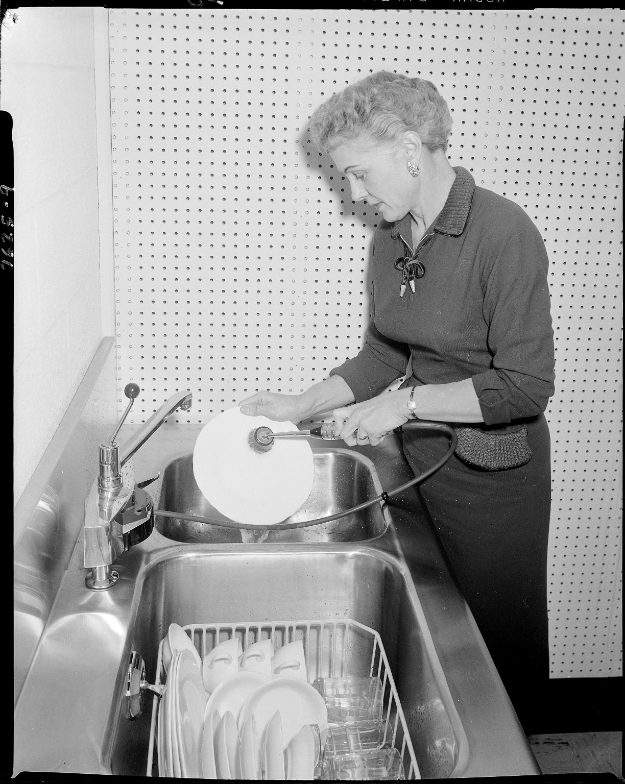 Ruud Manufacturing Company, in-sink dishwasher being demonstrated by model