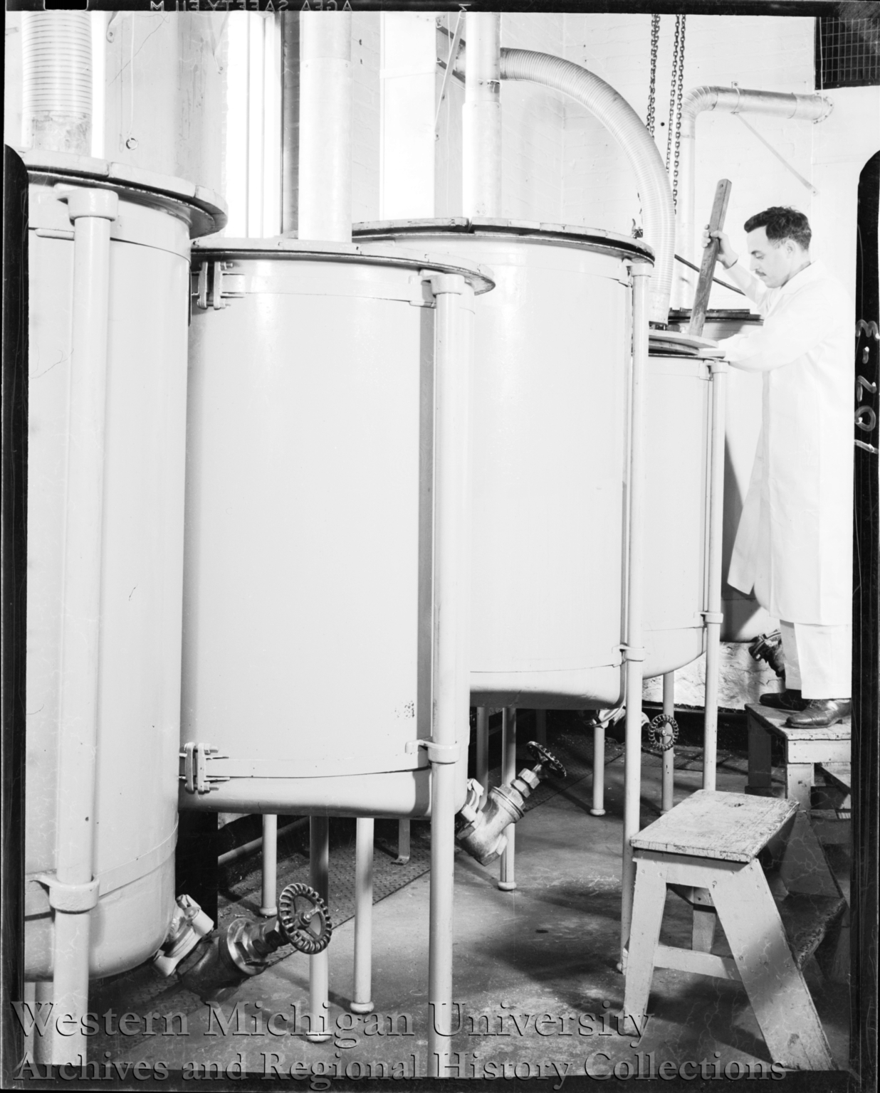 Pfaudler, technician mixing materials in a vat