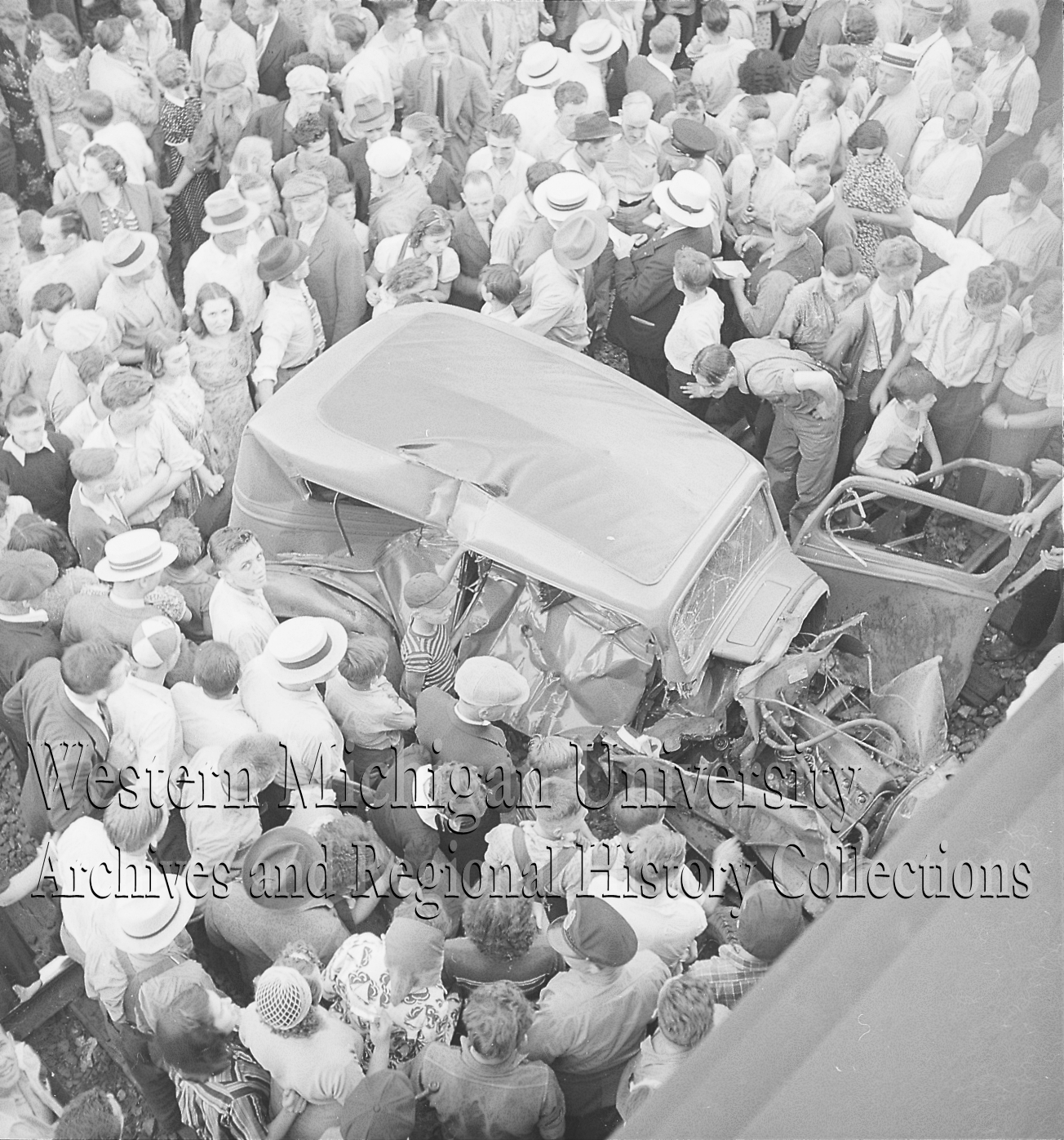 Crowd around an automobile and train car accident on the railroad tracks, overhead view