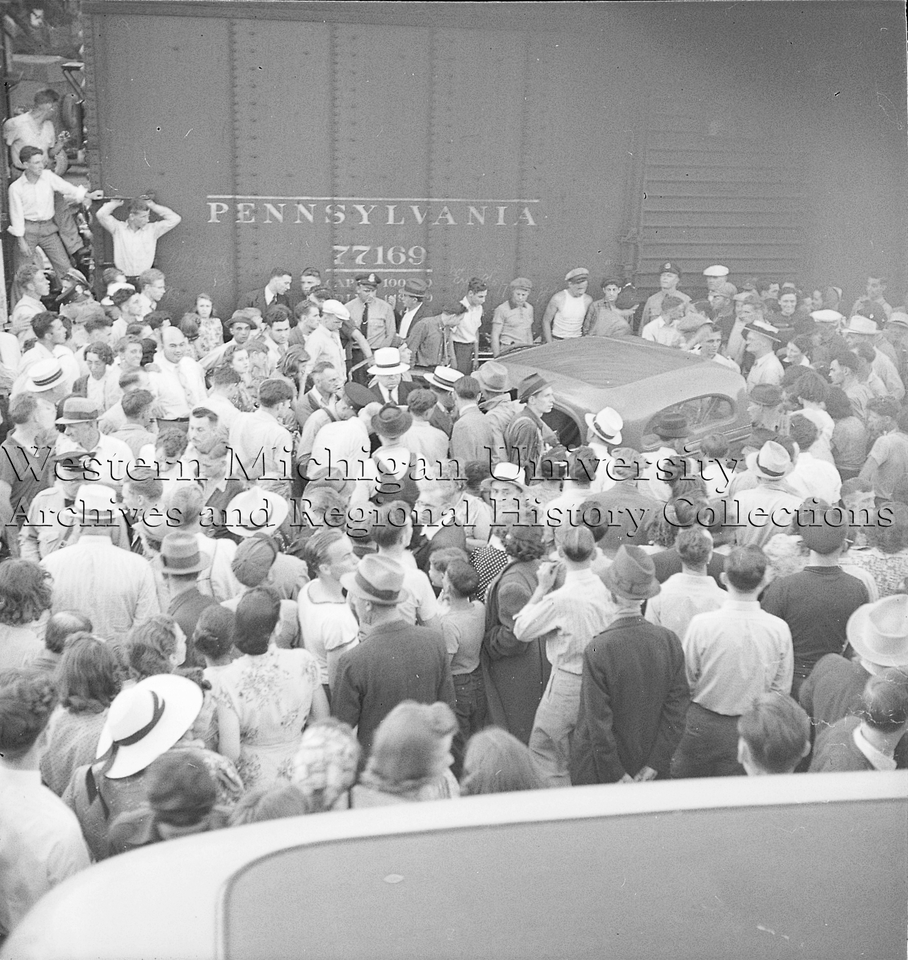 Crowd around an automobile and train car accident on the railroad tracks