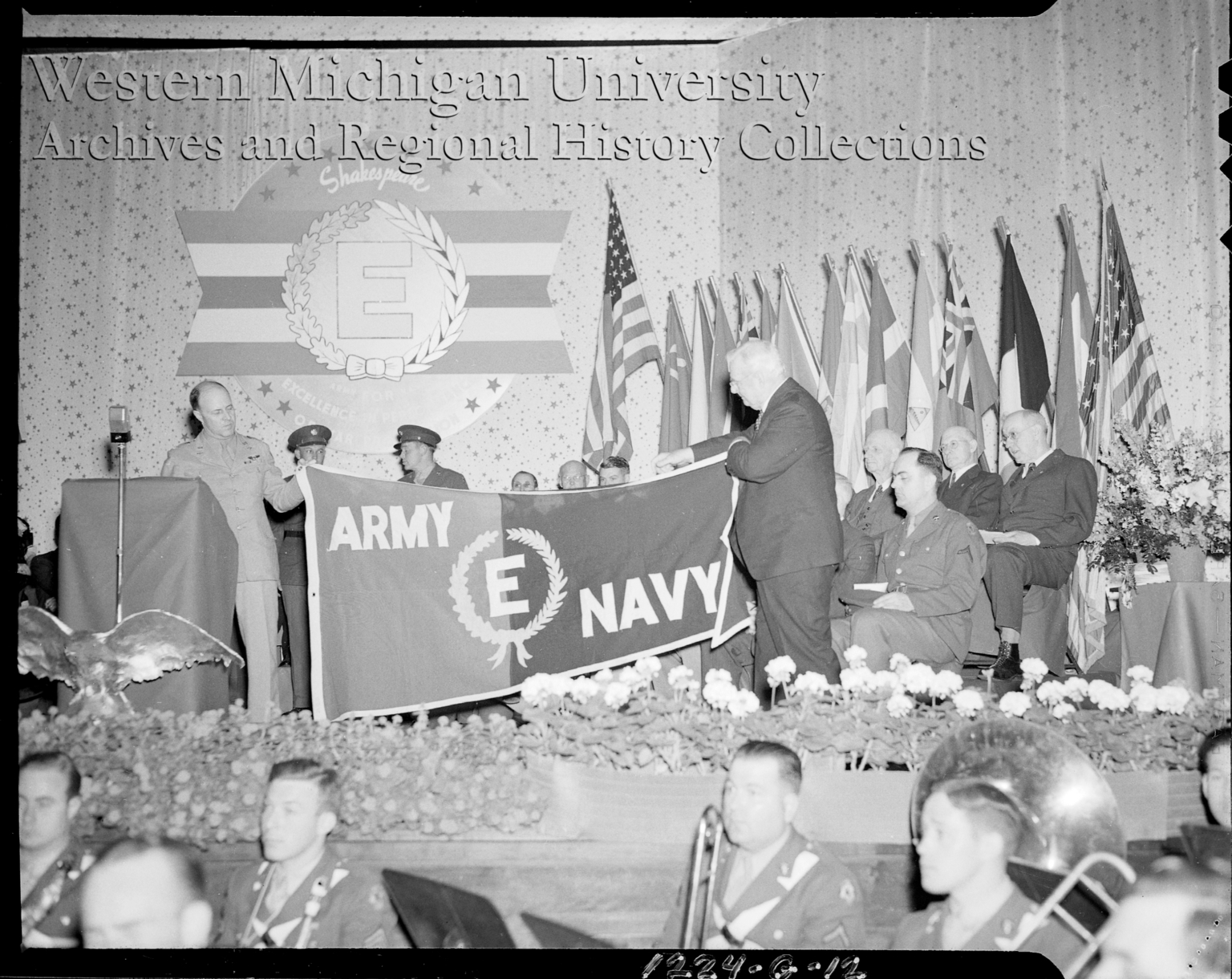 Shakespeare Company, men holding banner at the Army-Navy E Award Ceremony