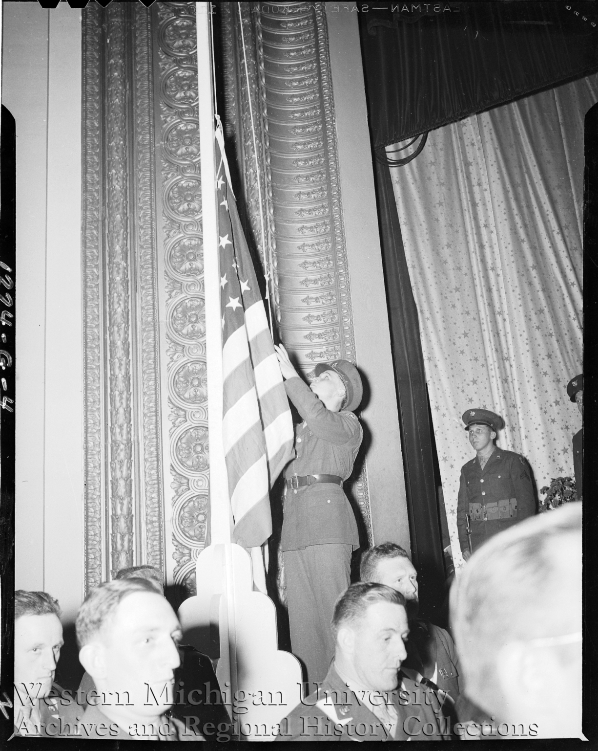 Soldier raising flag at the Army Navy E Award Ceremony