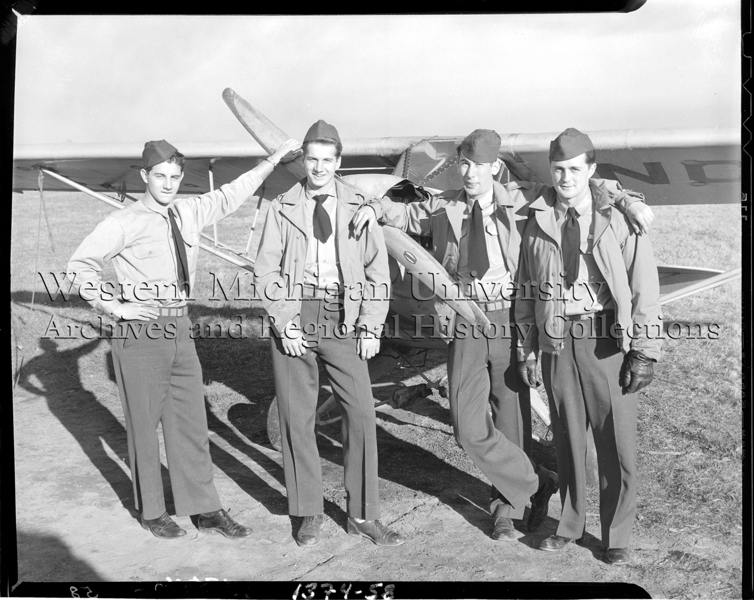 Western Michigan Flying Service, group of four flight cadets leaning on airplane