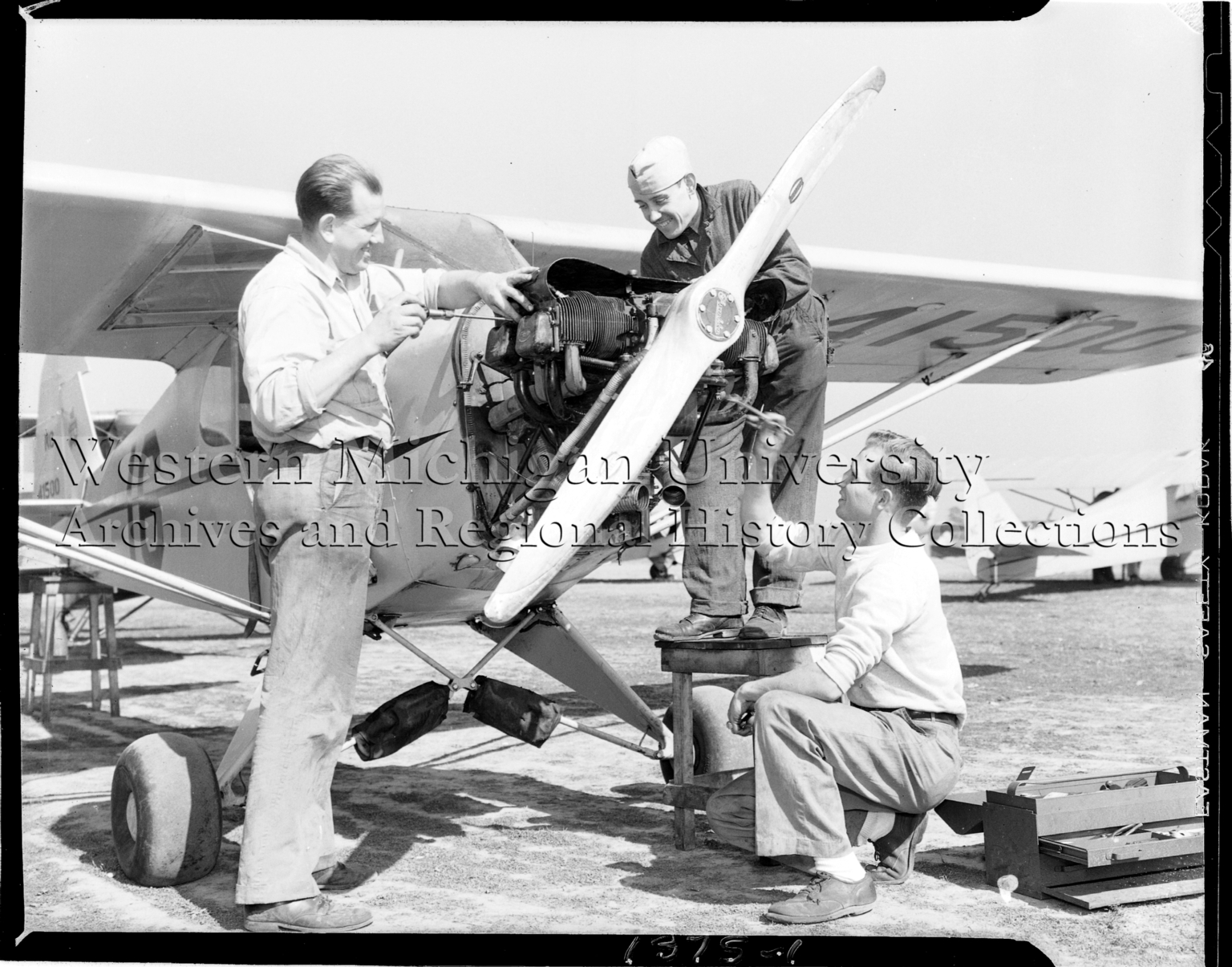 Western Michigan Flying Service, three mechanics working on airplane engine and propeller