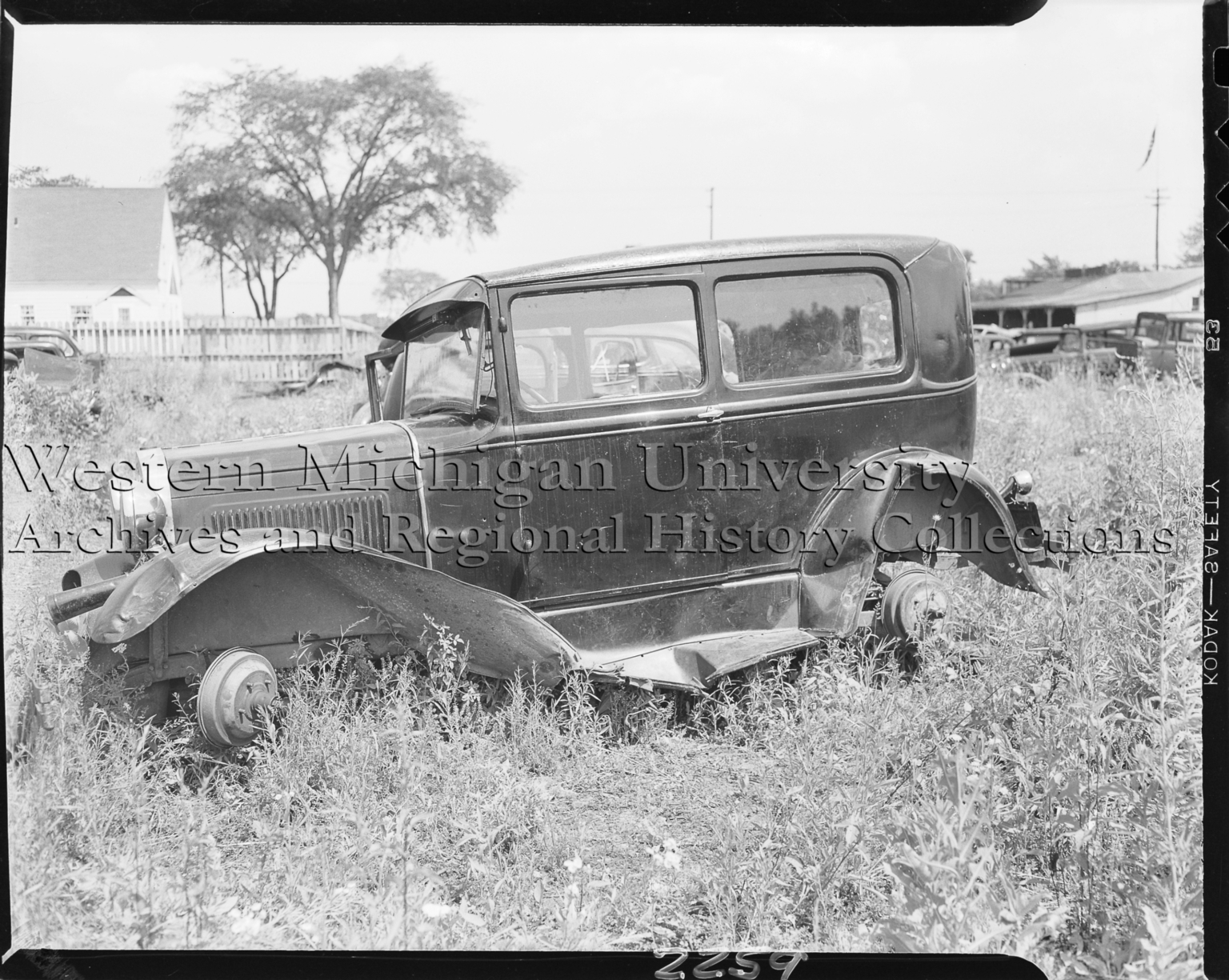 Wreck Ford Model A automobile in salvage yard