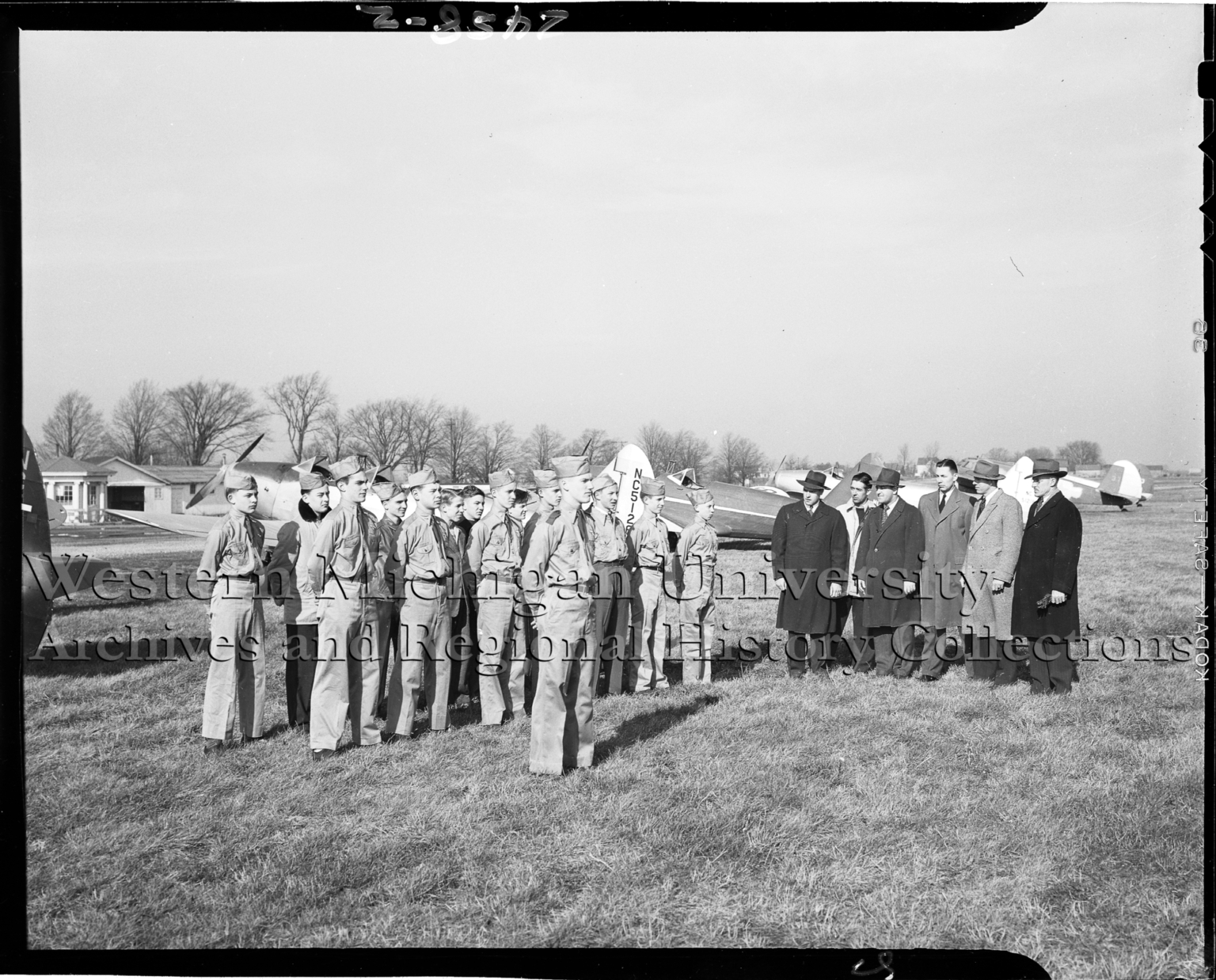 Air scouts standing at attention for inspection by men in winter coats