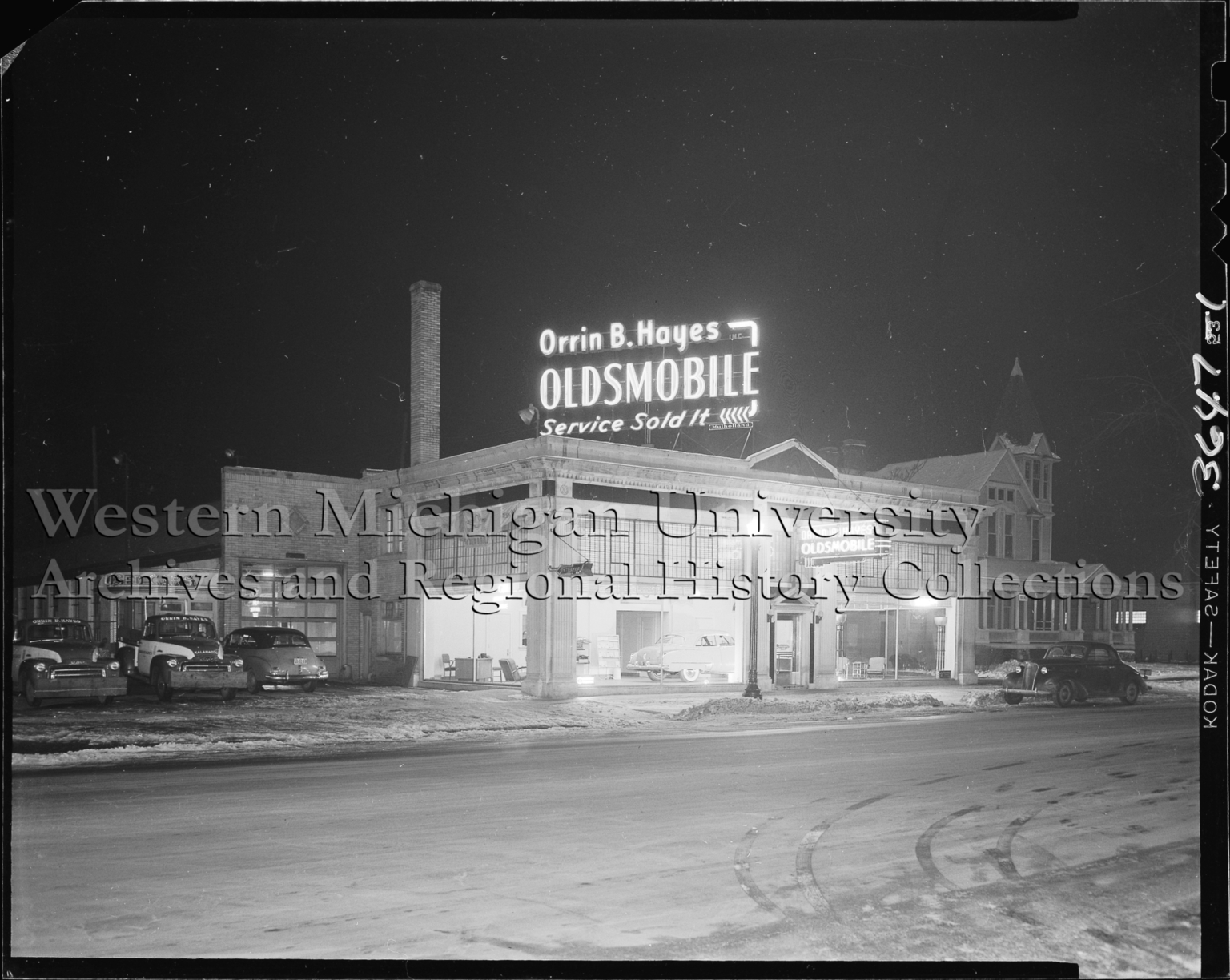 Orrin B. Hayes Oldsmobile dealership, exterior, at night, neon sign