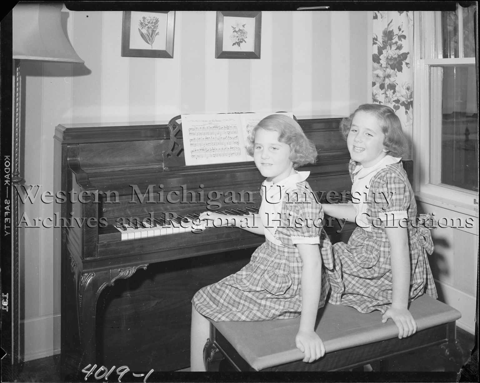 Two girls at a piano